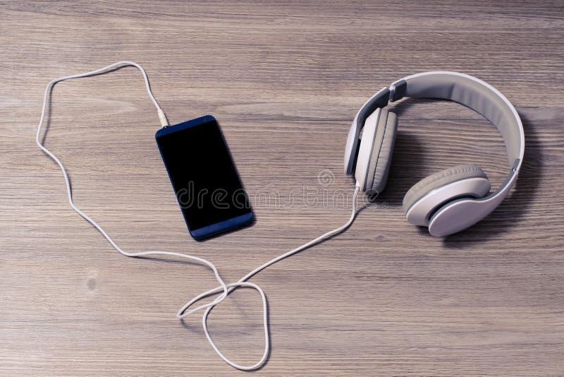 Los auriculares blancos y el teléfono móvil en un resto del ocio de la afición de la tabla relajan la educación de los auriculare imagen de archivo libre de regalías