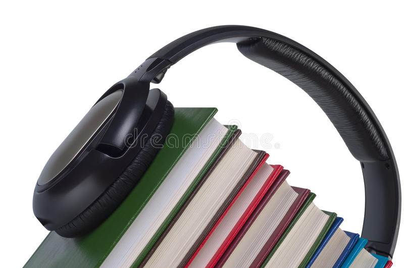 Los auriculares en los libros se cierran para arriba. fotos de archivo