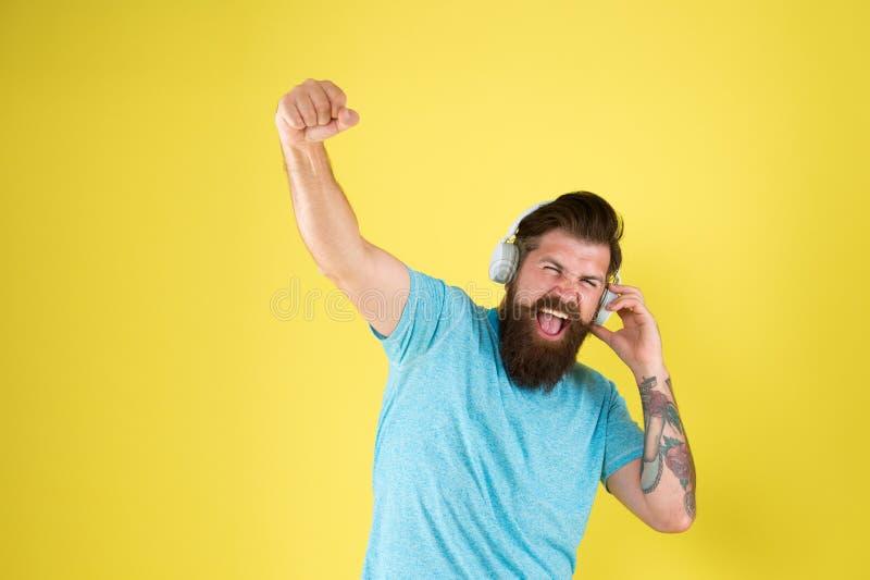 Los auriculares inalámbricos entregan el sonido limpio Inconformista feliz usando los auriculares inalámbricos modernos Ofertas i fotos de archivo
