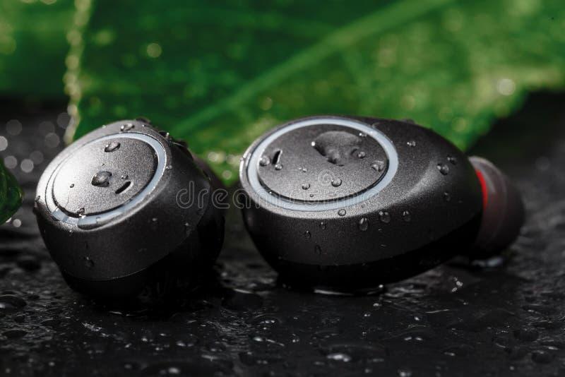 Los auriculares inalámbricos se cierran encima de la opinión sobre piedra negra fotografía de archivo