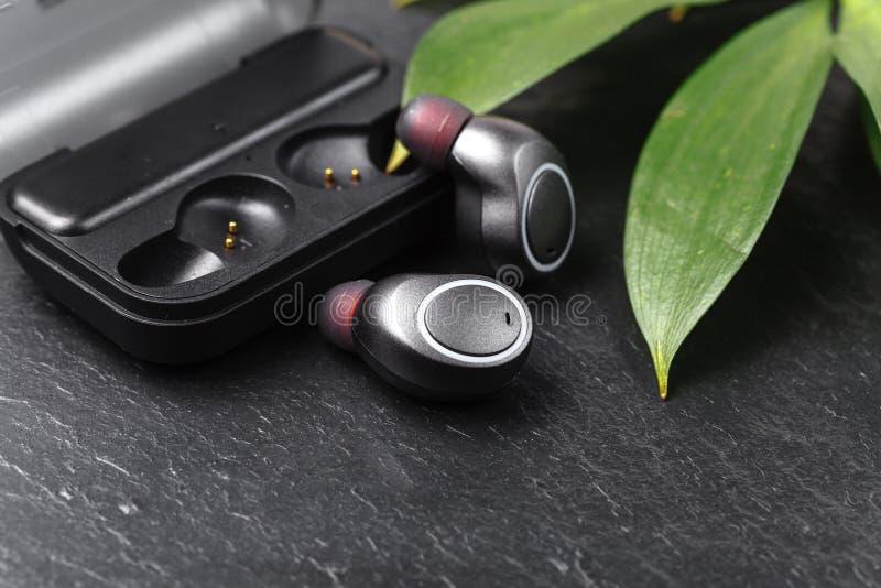 Los auriculares inalámbricos se cierran encima de la opinión sobre piedra negra fotos de archivo libres de regalías