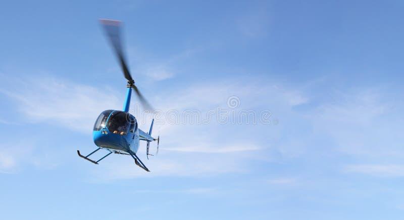 Los aviones - helicóptero azul de la vista delantera el pequeño hace vuelo de escasa altura fotografía de archivo