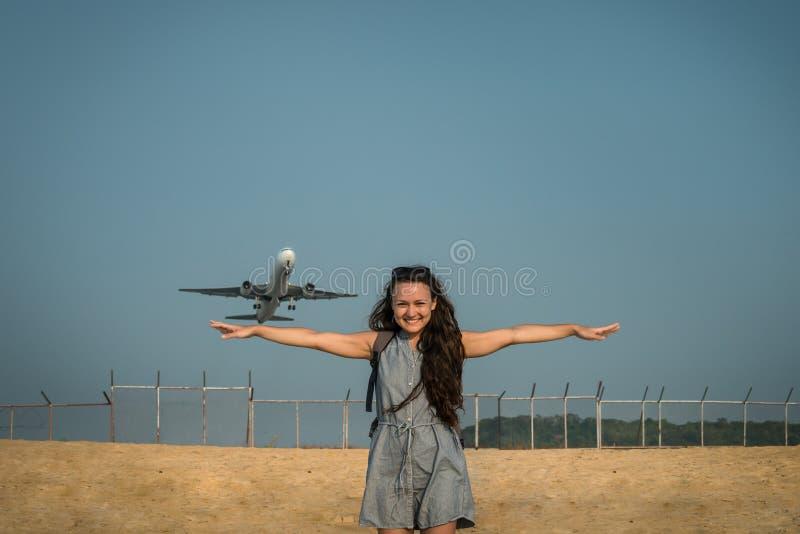Los aviones les gusta un pájaro El avión de reacción saca en el fondo detrás de una mujer joven imágenes de archivo libres de regalías