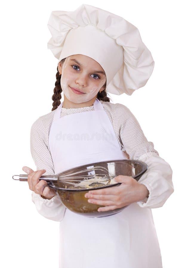 Los azotes del cocinero de la niña baten los huevos en una placa grande foto de archivo libre de regalías
