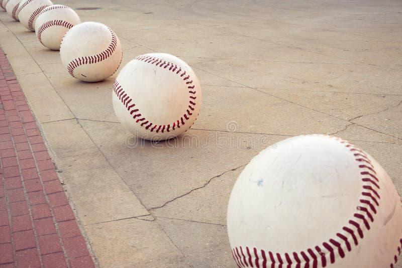 Los béisboles decorativos de gran tamaño forman una trayectoria a lo largo de una acera fotografía de archivo