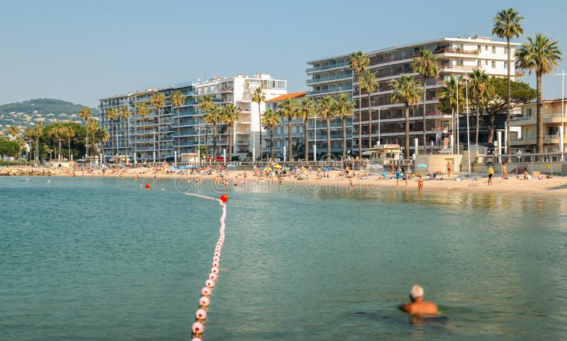 Los bañistas y la natación del sol de la madrugada en los pernos de los les de Juan varan, un destino popular del centro turístic imagenes de archivo