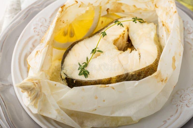 Los bacalaos cocieron en papel de pergamino con las rebanadas foto de archivo