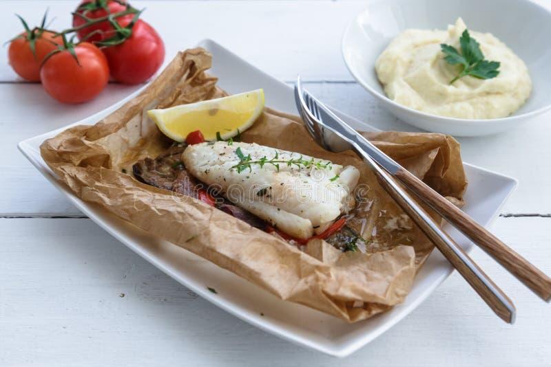 Los bacalaos cocieron en papel de pergamino con las verduras imagenes de archivo