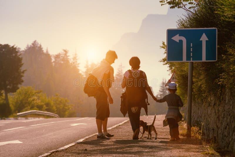 Los backpackers de la familia van en el camino en la puesta del sol imágenes de archivo libres de regalías