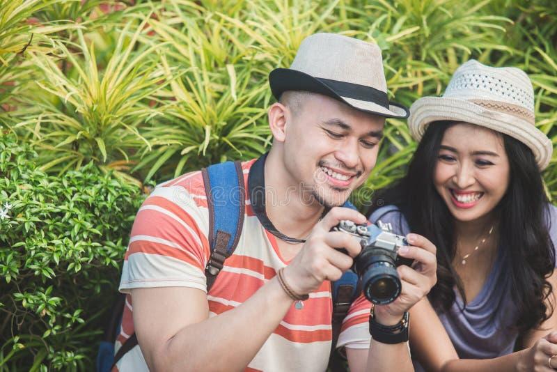 Los Backpackers se juntan ven el resultado de su foto en cámara imagenes de archivo