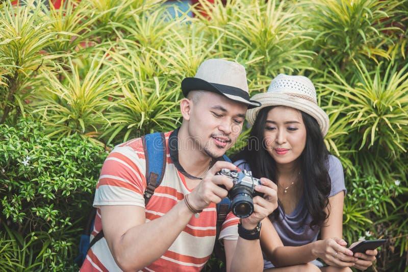 Los Backpackers se juntan ven el resultado de su foto en cámara imagen de archivo