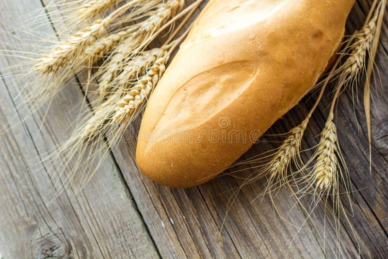 Los baguettes cocieron recientemente puntos del pan y del trigo en fondo de madera foto de archivo libre de regalías