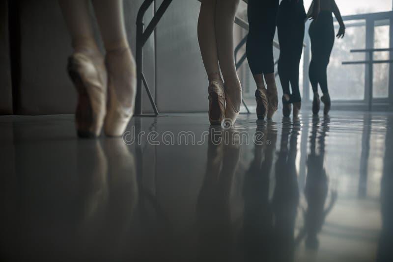 Los bailarines de ballet hacen una pausa la barra del ballet foto de archivo
