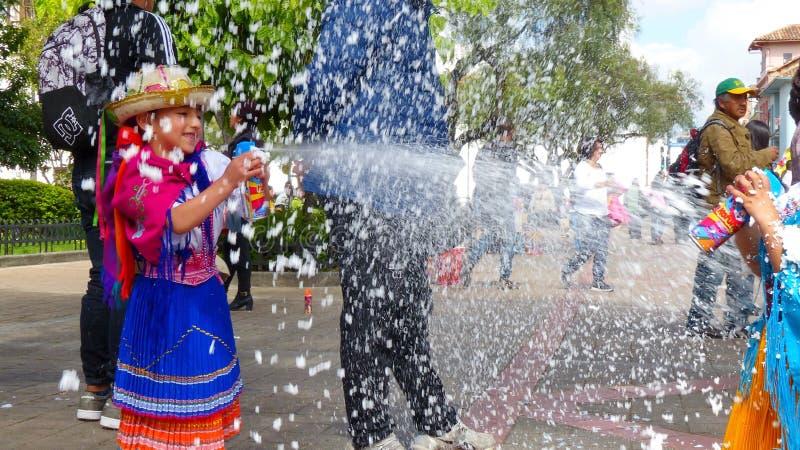 Los bailarines de las niñas están rociando espuma en uno a en el carnaval imagen de archivo