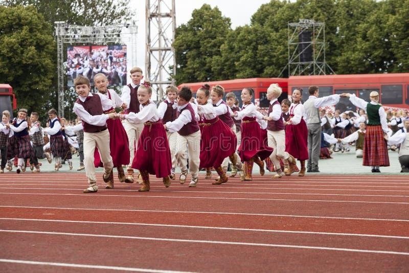 Los bailarines en trajes tradicionales se realizan en el concierto magnífico de la danza popular de la canción letona de la juven foto de archivo libre de regalías