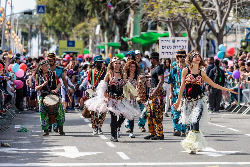 Los bailarines en vestidos multicolores participan en el carnaval anual de Adloyada se vistieron como los exploradores van con lo imagenes de archivo
