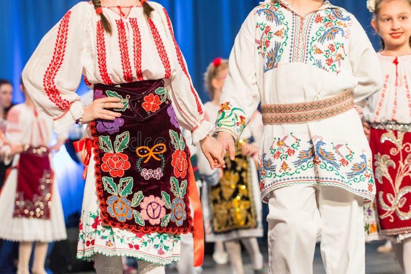 Los bailarines rumanos jovenes realizan una danza popular en traje folclórico tradicional Folclore de Rumania foto de archivo libre de regalías