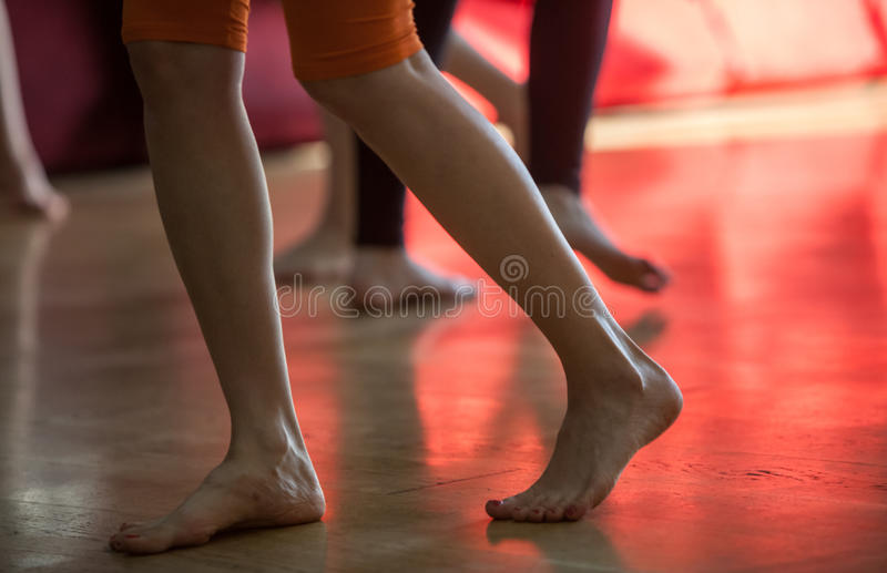 los bailarines se alzan, las piernas, en piso imagen de archivo