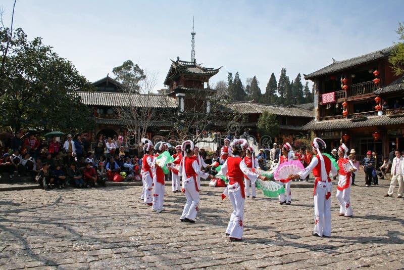 Los bailarines tradicionales de un grupo minoritario se realizan en la ciudad vieja de Lijiang imagen de archivo