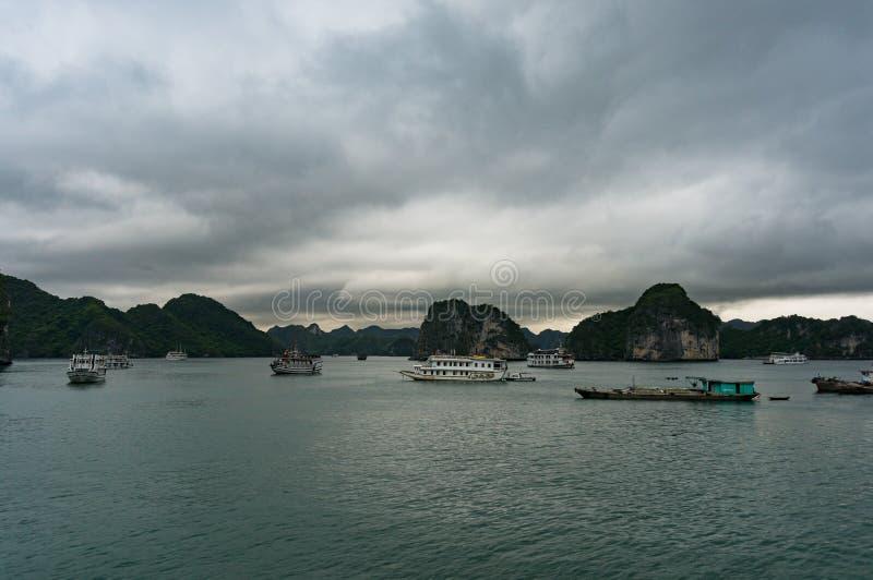Los barcos de cruceros y los barcos de la travesía en Halong aúllan, Vietnam fotografía de archivo