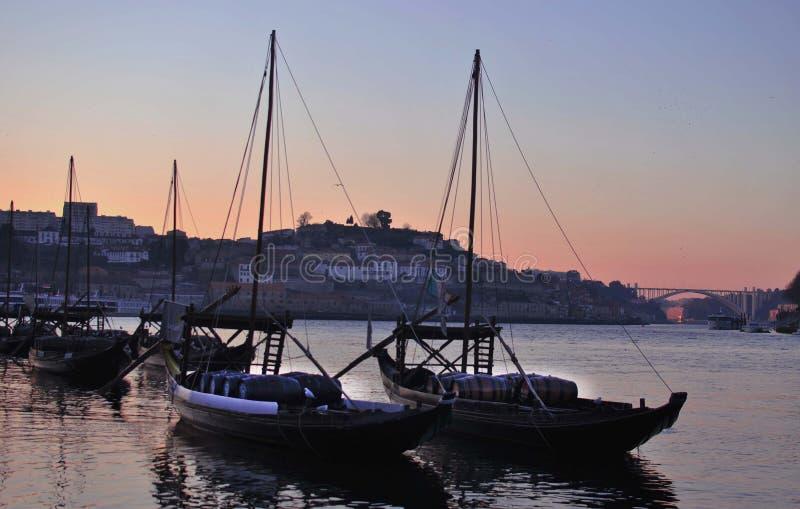 Los barcos de navegación cargados con los barriles se colocan en un pequeño puerto en el sunse fotos de archivo libres de regalías