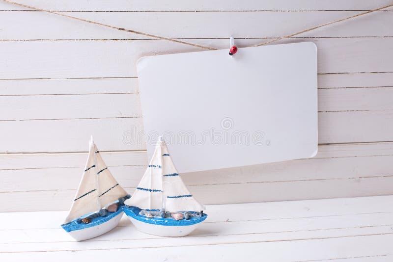 Los barcos de navegación de madera decorativos de los juguetes y el Empty tag encendido visten imagen de archivo libre de regalías