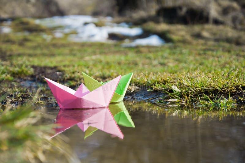 Los barcos de papel coloreados flotan en los charcos tempranos de la primavera foto de archivo