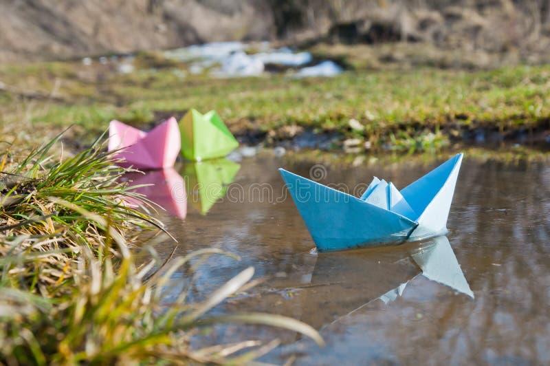 Los barcos de papel coloreados flotan en los charcos tempranos de la primavera fotografía de archivo libre de regalías