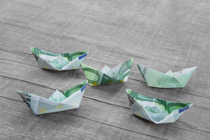 Los barcos de papel doblaron fuera del dinero en un fondo de madera gris fotografía de archivo libre de regalías