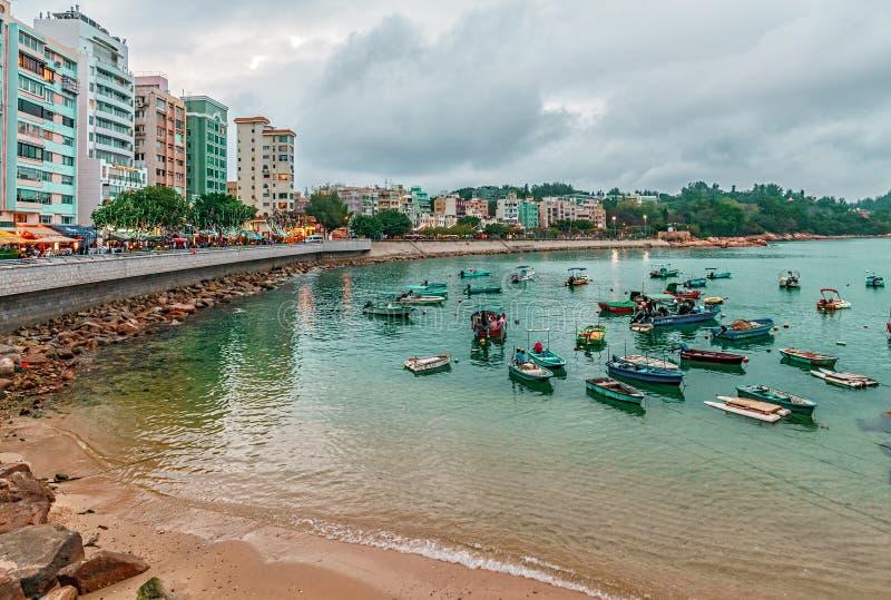Los barcos de pesca descansan en Stanley Bay al lado de la costa en fondo de los edificios Paisaje escénico hermoso de la costa d imagen de archivo libre de regalías