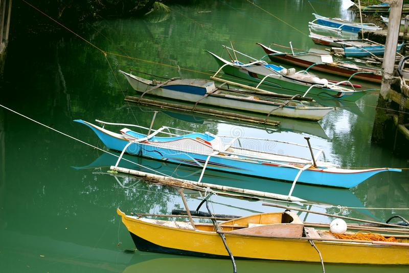 Los barcos de pesca filipinos tradicionales se colocan en la bahía cerca de la costa imágenes de archivo libres de regalías