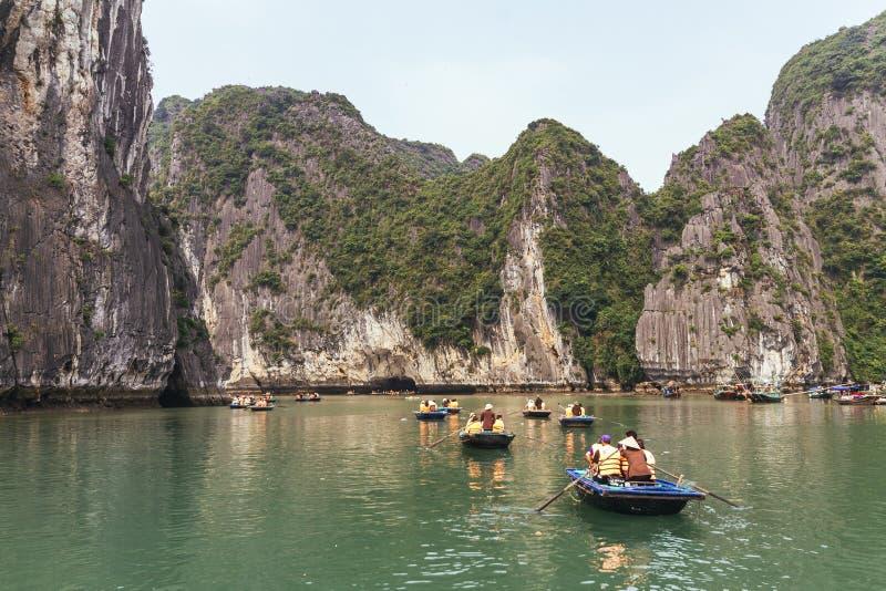 Los barcos de rowing con muchos turistas que viajan dentro de la piedra caliza excavan con la isla de la piedra caliza en fondo e fotografía de archivo