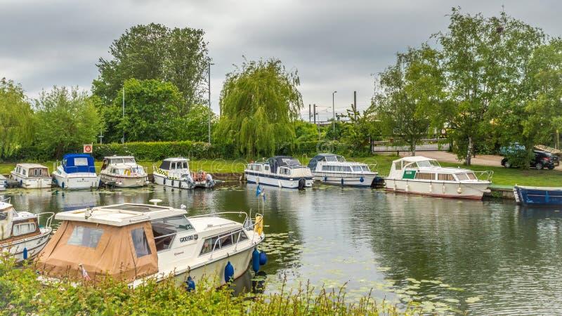 Los barcos de tipos y de tamaños de diferenciación alinean los bancos del río gran Ouse en Ely imagenes de archivo