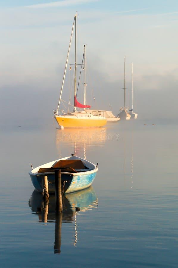 Los barcos en el lago por mañana brumosa amanecen fotografía de archivo