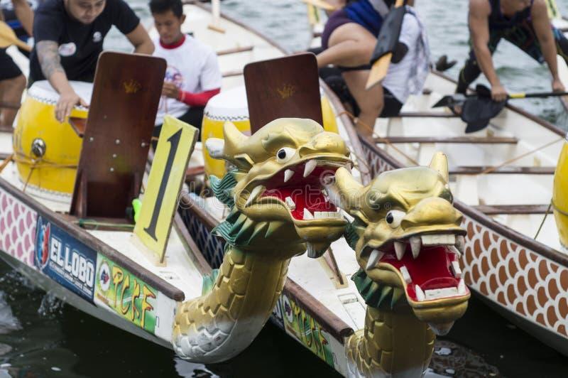 Los barcos nativos de la cabeza del dragón de la fila de los deportes parqueados en el lago apuntalan durante Dragon Cup Competit imagen de archivo