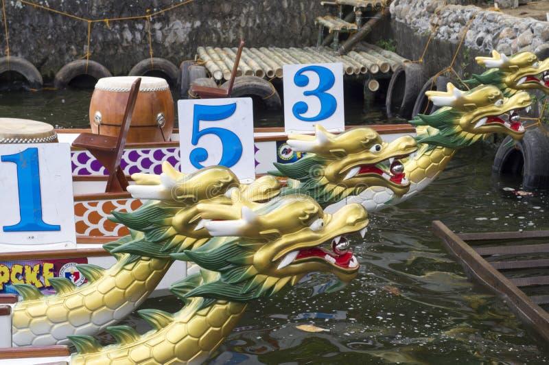 Los barcos nativos de la cabeza del dragón de la fila de los deportes parqueados en el lago apuntalan durante Dragon Cup Competit imagen de archivo libre de regalías
