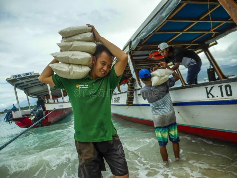 Los barcos suministran 24/7 de toda la clase de materia para compensar la falta de recursos de la isla Aquí el equipo que descarg imagen de archivo