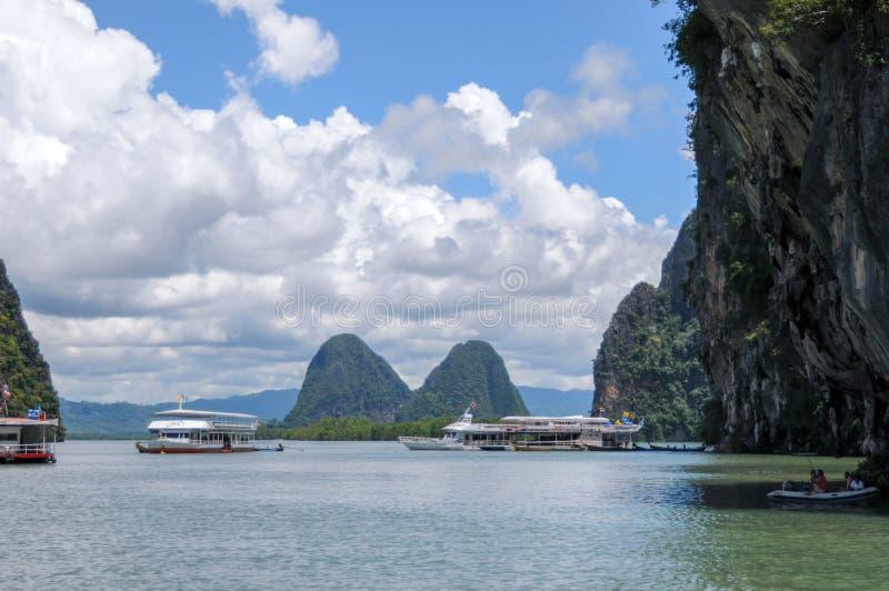Los barcos turísticos en la bahía cerca de las islas del karst foto de archivo