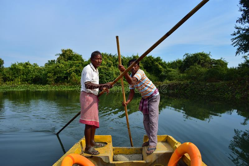 Los barqueros conducen el barco a través de Buxa Tiger Reserve en Bengala Occidental, la India Un paseo del barco a través de la  fotografía de archivo libre de regalías