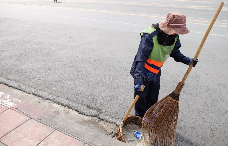 Los barrenderos de calle limpian en un camino imagenes de archivo