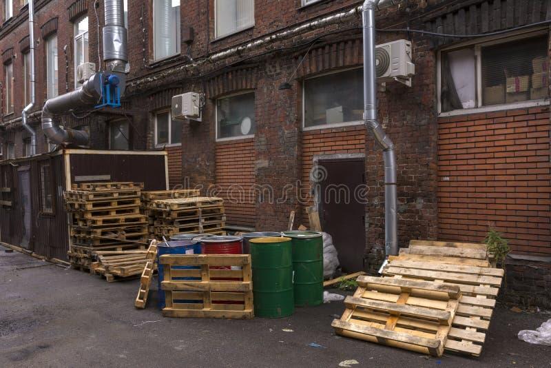 Los barriles y paletas están en el patio del almacén imagenes de archivo