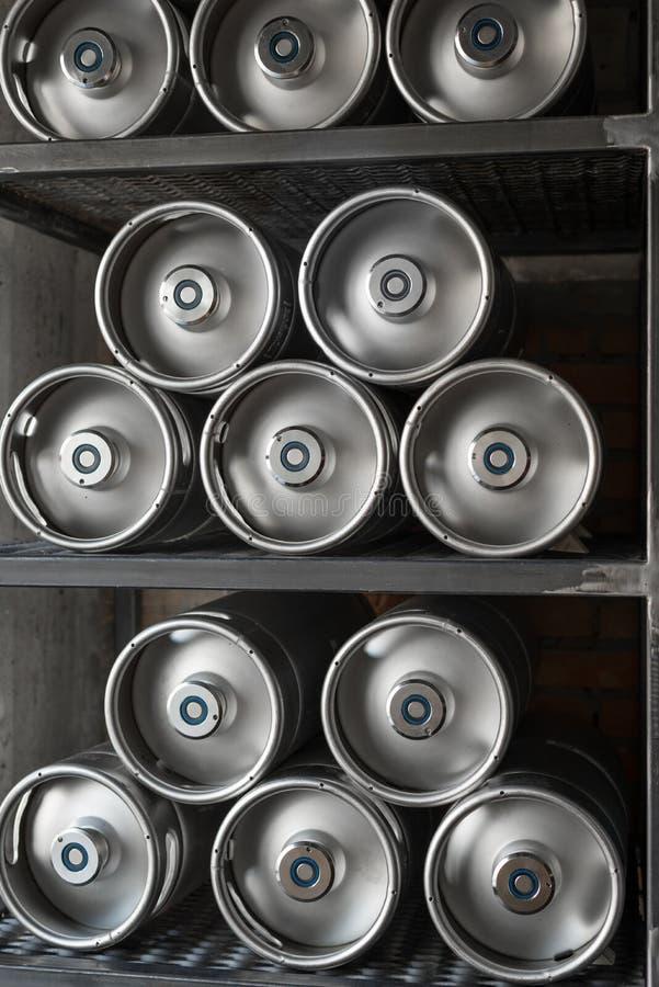 Los barriletes de cerveza del metal mienten en fila imágenes de archivo libres de regalías