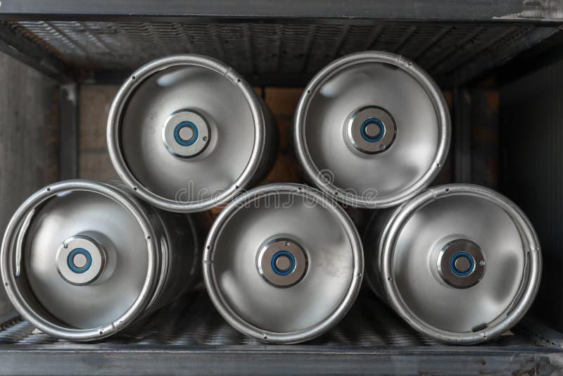 Los barriletes de cerveza del metal mienten en fila foto de archivo