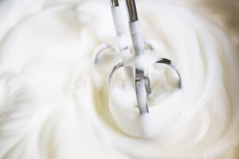 Los batidores del mezclador emersed en parte en las claras de huevo azotadas acaban de batirse que hasta que sean tiesos imagen de archivo