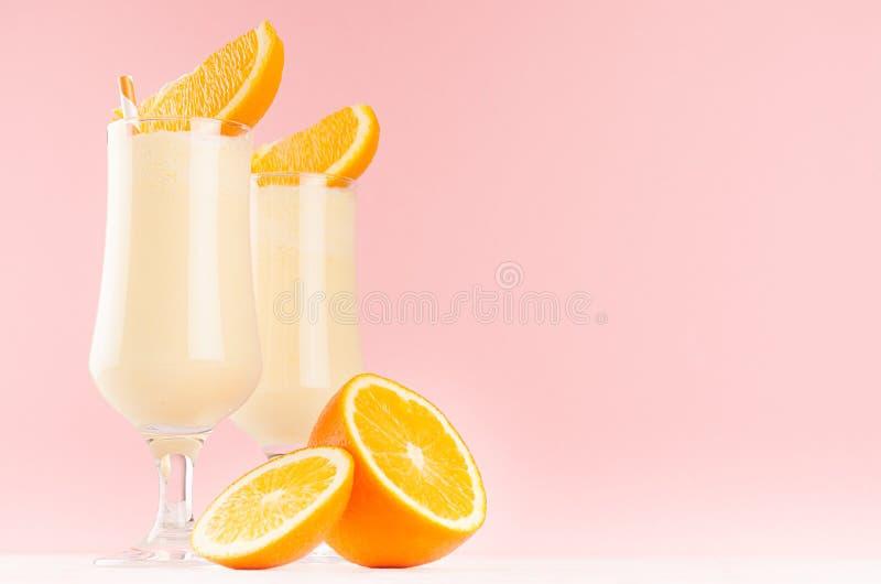 Los batidos de leche alegres dulces adornaron la fruta de las rebanadas, paja rayada en fondo rosado en colores pastel ligero imagenes de archivo