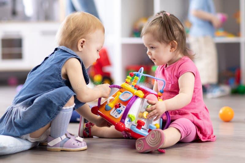 Los bebés están en conflicto en cuarto de niños El niño está intentando llevarse el juguete de otro niño imagen de archivo