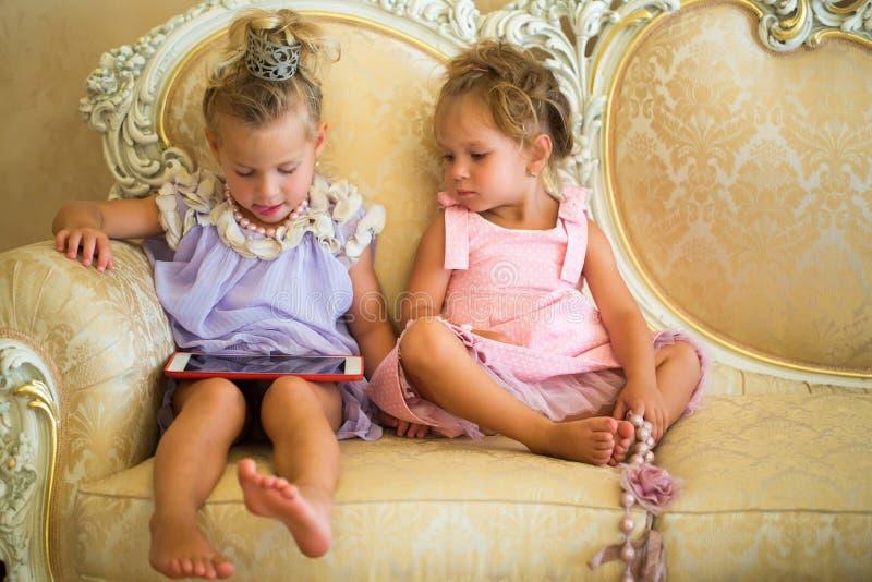 Los bebés se sientan en el sofá clásico fotografía de archivo libre de regalías