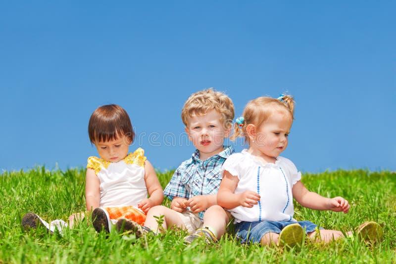 Los bebés se sientan en hierba fotografía de archivo