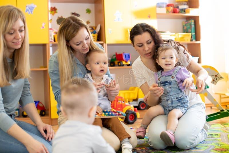 Los beb?s con sus madres juegan con los juguetes en cuarto de ni?os imagen de archivo