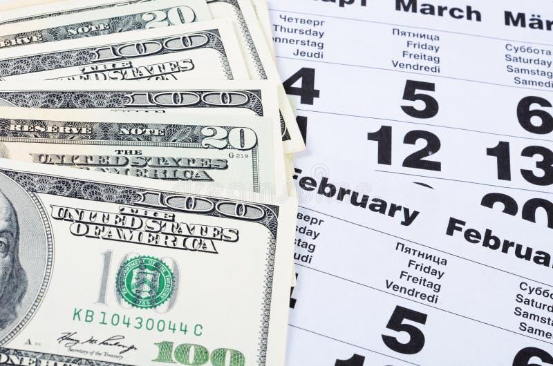 Los billetes de banco de dólares en calendario cubren el primer fotografía de archivo libre de regalías